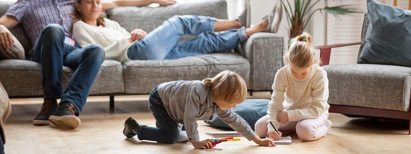 Two kids playing in living room while parents watch