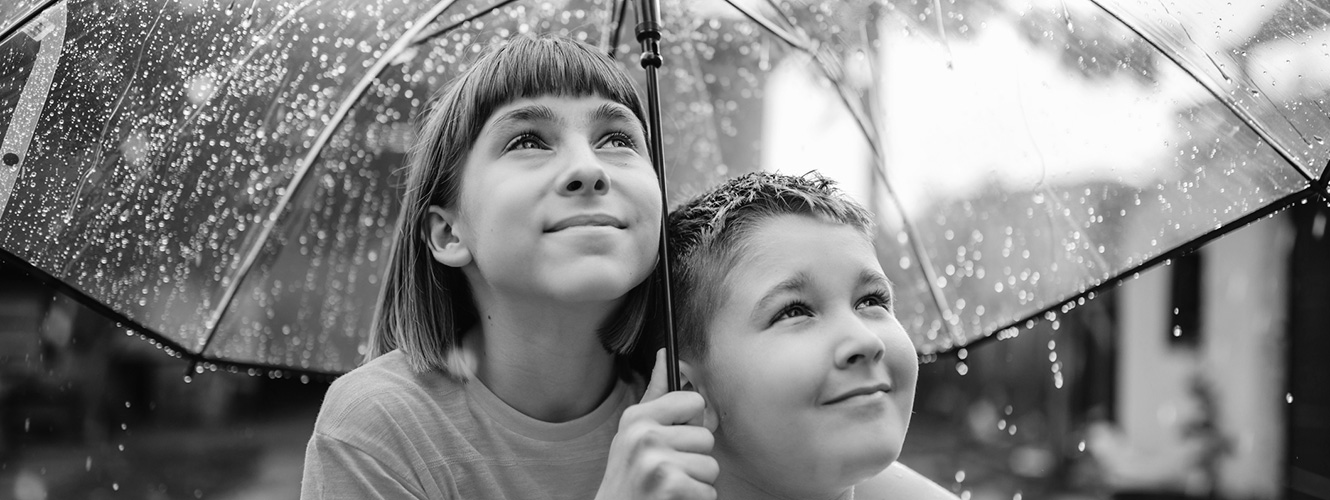 Two kids under umbrella